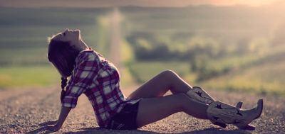 девушка сидит на дороге и смотрит на небо