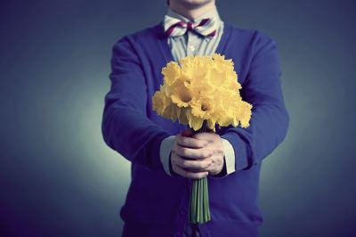 парень преподносит желтые цветы